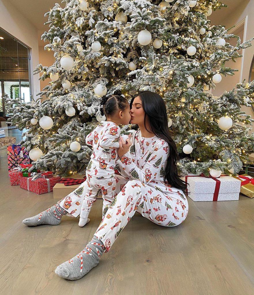 kylie e Stormi posam junto à árvore de Natal.