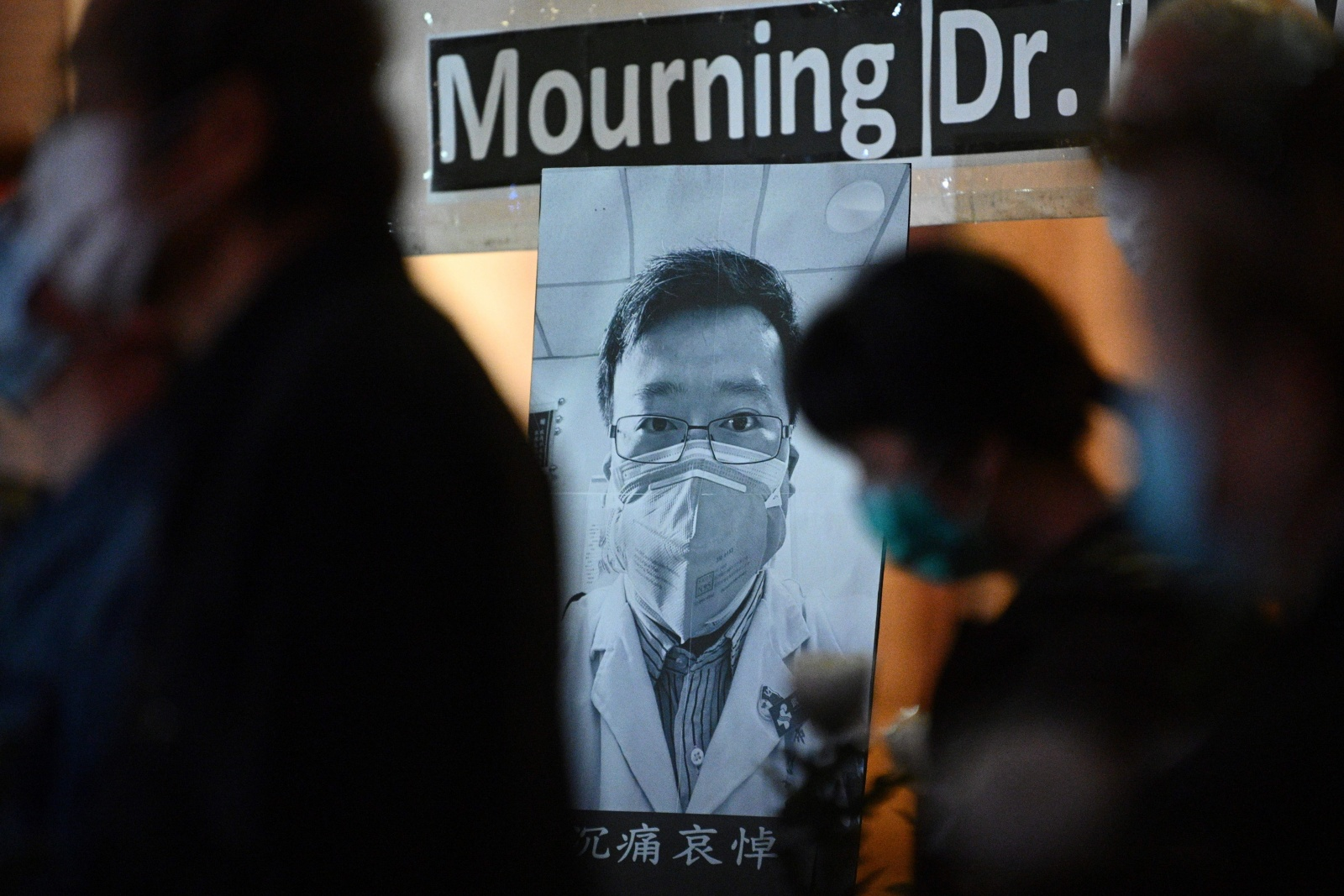 People attend a vigil in Hong Kong on February 7, 2020 for novel coronavirus whistleblowing doctor Li Wenliang (pictured background C), 34, who died in Wuhan after contracting the virus while treating a patient. - A Chinese doctor who was punished after raising the alarm about China's new coronavirus died from the pathogen on February 7, sparking an outpouring of grief and anger over a worsening crisis that has now killed more than 630 people. (Photo by Anthony WALLACE / AFP) (Photo by ANTHONY WALLACE/AFP via Getty Images)