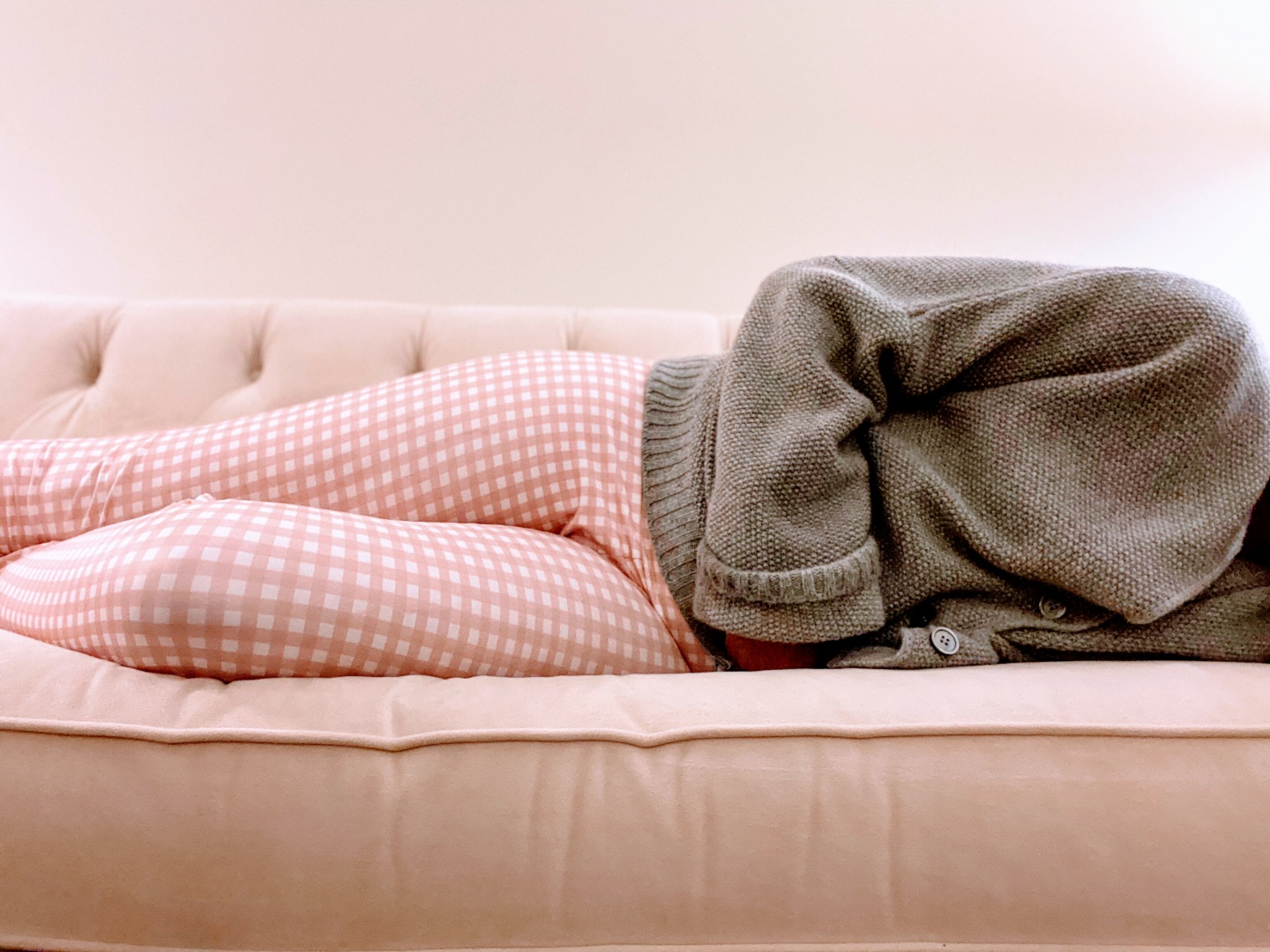 mid adult woman clutches stomach while lying down on couch