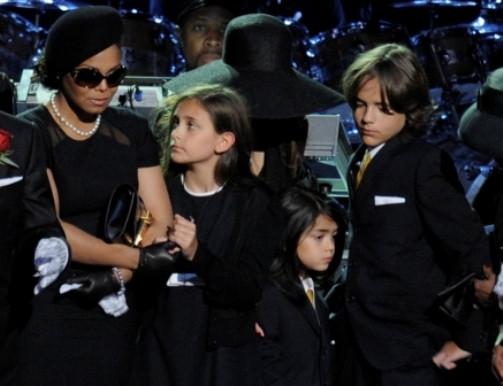 As crianças acompanhadas de Janet Jackson no funeral do pai